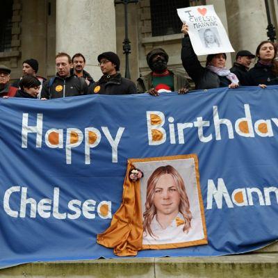 Ihmiset pitävät käsissään banderolleja, joissa lukee happy birthday ja on kuvia vangitusta Manningista.