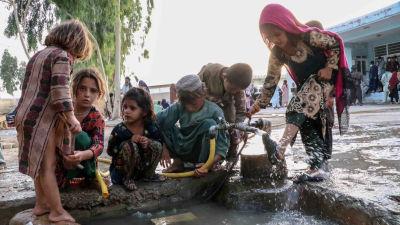 Barn tvättar sig vid en brunn på ett flyktingcenter i Kandahar i Afghanistan