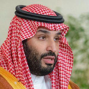 Muhammad bin Salman sitter vid ett skrivbord och håller tal.