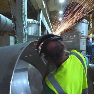 Mies hitsaa metallia tehtaalla.