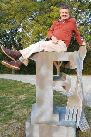 Kettil Cedercreutz poserar på staty föreställande en F-bokstav samt kniv och gaffel.