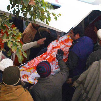 Sukulaiset nostavat menehtyneet avustustustyöntekijän ruumista ambulanssiin Swabin kaupungissa Pakistanissa.