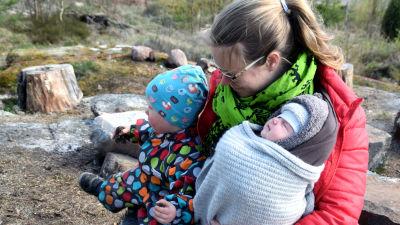 En kvinna sitter utomhus med en sex veckor gamla baby i famnen. Bredvid dem sitter ett två år gammalt barn i en prickig overall.