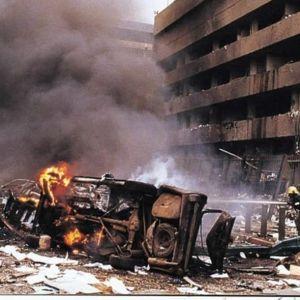 Efter attackerna i Nairobi 1998. Ett bombaderat hus med bilskrot som exploderat framför sig. Ett rökmoln och brandmän som släcker elden