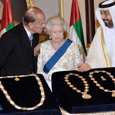 Sheikki Khalifa bin Zayed Al Nahyan esittelee kuningatar Elisabetille ja prinssi Philipille kolmea kaulaketjua ja kunniamerkkejä, jotka ovat samettialustalla.
