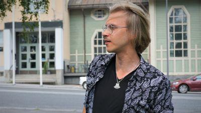 Ung blond man med glasögon står vid en gata.