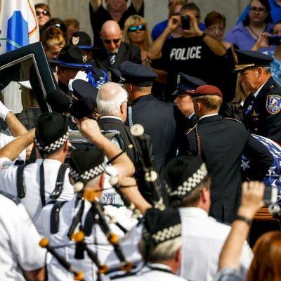Suuri joukko poliiseja tekee kunniaa kuolleen poliisin arkulle.