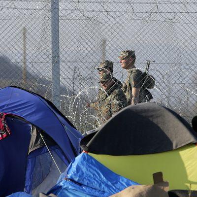 Siirtolaisten telttaleiri ja sotilaita.