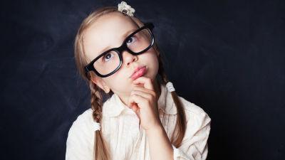 En flicka med flätor och glasögon står och funderar på något.
