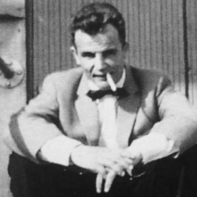 mies istuu portailla tupakka suussa, mustavalokuva