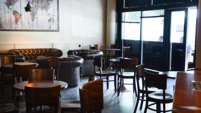 Hotelli Zilton pubben inifrån. På bilden syns ett mörkt rum fullt med bord och stolar och i bakgrunden skymtar uteterassen.