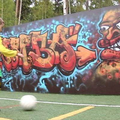 Poika potkaisee jalkapalloa graffitiseinää vasten.