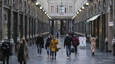 Bild på personer med ansiktsskydd som går inne i shoppingscenter i Bryssel.
