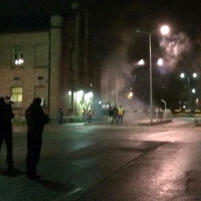 Poliiseja ja mielenosoittajia Hennalan entisen kasarmialueen portilla.