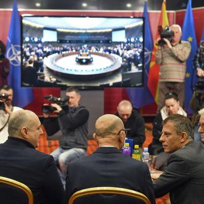 Kuvassa etualalla neljä miestä istumassa. Taustalla suuri näyttö ja kuvaajia.