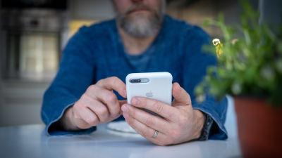 En man i närbild använder en mobiltelefon.