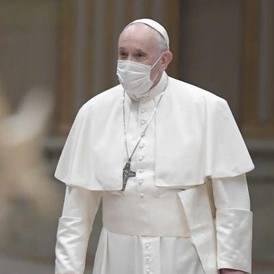 Påven Franciskus, med ett munskydd på ansiktet, med en julgran i förgrunden.