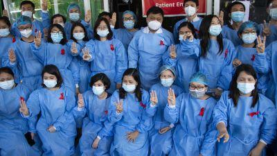 Terveydenhoitohenkilökunta tekee kolmen sormen tervehdyksen helmikuussa Yangonissa.