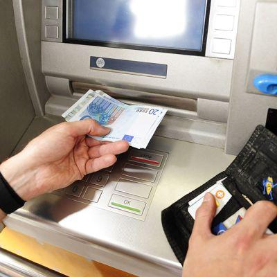 Mies nostaa käteistä pankkiautomaatilla.