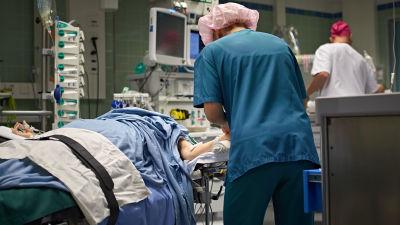 Operationssal med patient, läkare och sjukskötare i salen.