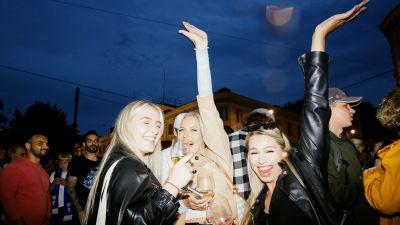 Tre kvinnor firar fotbollsherrarnas vinst. De posterar med händerna i luften.