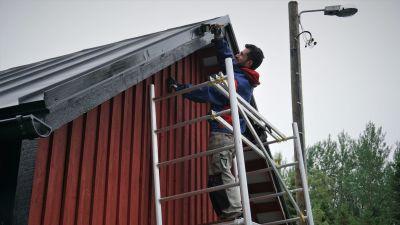 En man står på en byggställning och målar taket på ett hus.