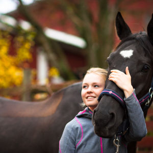 Vaalea nainen halaa hevosen päätä