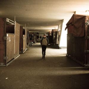 nainen kävelee tallissa