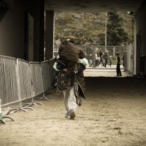 hoitaja kantaa loimea ratsastuskilpailuissa