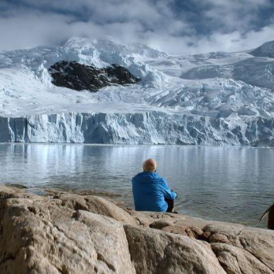 Jäätikkötutkija Claude Lorius ja pingviini Antarktiksella.