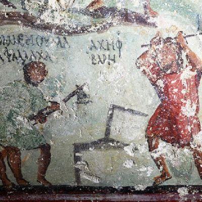 Seinämaalaus kahdesta kivenhakkaajaasta työssään. Molempien vieressä kreikkalaisilla kirjaimilla kirjoitettua tekstiä.