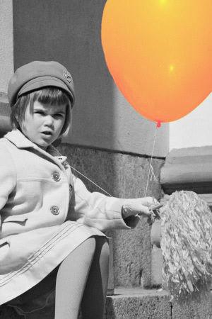 Pikkutyttö istuu vapunpäivänä ilmapallo ja vappuviuhka kädessään Tuomiokirkon portailla..