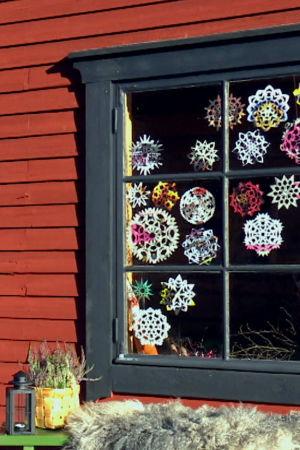 Ett fönster med svart foder, karm och spröjs. Fönstret är dekorerat med nästan tjugo papperssnöflingor i olika mönster och färger. Framför fönstret står en bänk med ett fårskinn, en svart stallykta och en spånkorg med ljung. Bilden är tagen från utsidan.