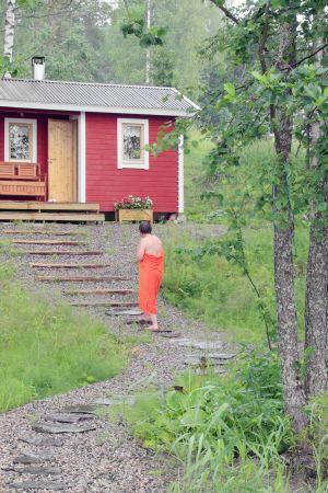 Nainen kävelee kesämökin pihalla.