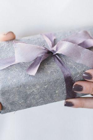 Naisella lahjapaketti käsissään.