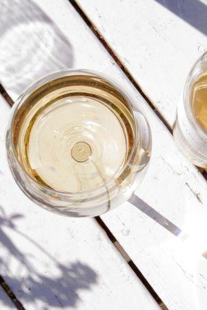 valkoviinipullo ja viinilasi pöydällä
