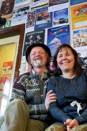 Mies ja nainen istuvat vierekkäin penkillä ja heidän taustalla on seinä täynnä julisteita