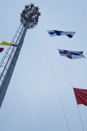 Itsenäisen Suomen kolme lippua nostettuna valomastoon.