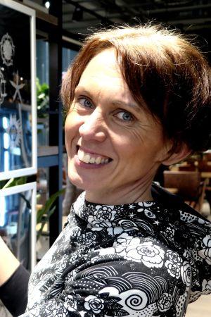 Kristiina Töyli hymyilee näyttelyyn ripustettujen taulujen edessä.