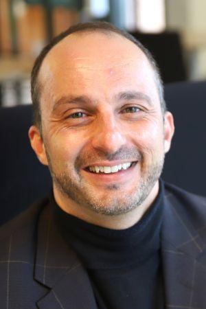 Hymyilevä mies istuu penkillä
