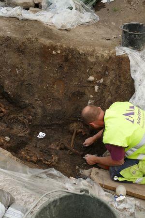 Kuopan pohjalle polvistunut tutkija kaapii maata luiden päältä.