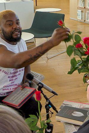 Rap-artisti Seksikäs-Suklaa (oik. Luyeye Konssi) ojentaa punaista ruusua rakkausrunoa kuuntelemaan jääneelle rouvalle keskustakirjasto Oodissa 1.8.2019  Puoli seitsemän -ohjelman Lukuhaaste-tempauksessa.