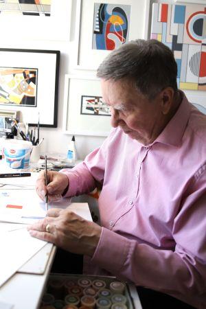 Kuvassa mies maalaa taideteosta