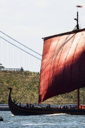 Iso punapurjeinen viikinkineve purjehtii sillan ohi.