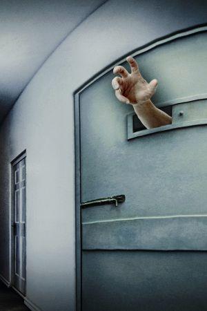 Käsi kurkottaa eristyshuoneen luukusta.