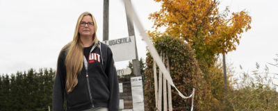 """Kvinna står intill en infart. Vid infarten hänger ett vitt plakat där det står """"STÄNGT CLOSED SULJETTU"""" med stora bokstäver."""