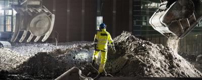 Rakennustyöläinen kävelee pimeässä kahden kaivinkoneen kauhan välissä.