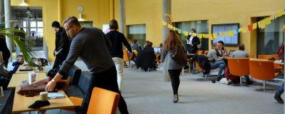 många studenter befinner sig i aulan av asa-huset. där finns stolar och bord i gulaktiga färger
