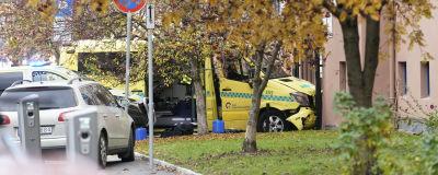 En ambulans med tillknycklad framdel mot en husvägg.