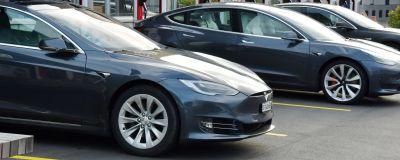 Tre Teslabilar parkerade vid laddningsstationer.